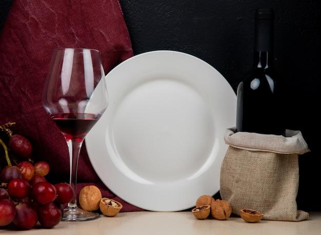 Vista del primo piano di vino rosso e del piatto vuoto con l'uva e la noce su superficie bianca e su fondo nero