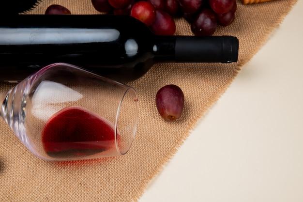 Vista del primo piano di vino rosso e dell'uva su tela di sacco su fondo bianco