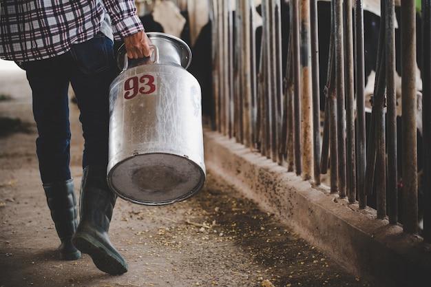 Vista del primo piano sulle gambe del coltivatore che lavora con il fieno al granaio animale