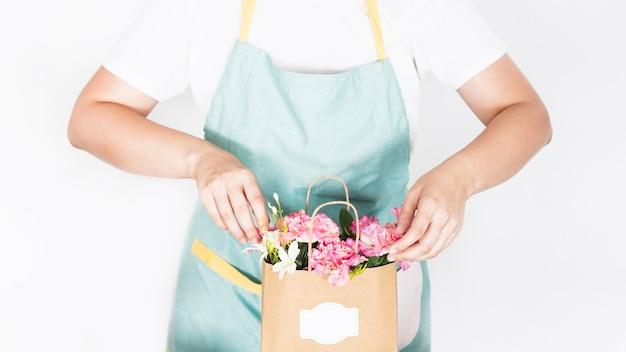 Vista del punto di vista di una mano femminile con il sacco di carta del fiore