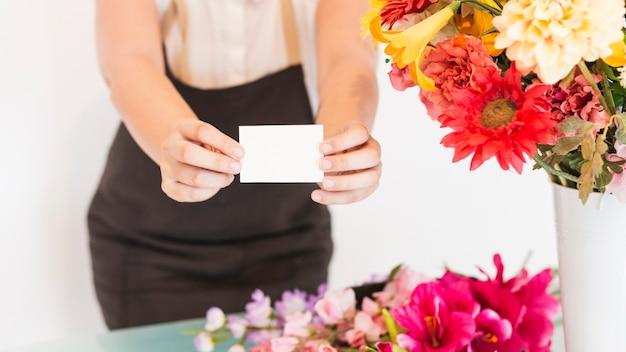 Vista del punto di vista di una mano femminile del fiorista con il biglietto da visita bianco in bianco