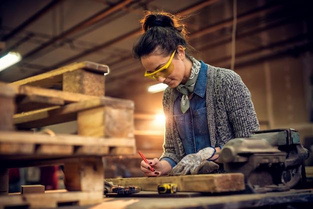 Vista del ritratto del lavoratore di carpenteria femminile professionale invecchiato mezzo sorridente soddisfatto con un disegno a matita sulla misura di nastro e di legno, morsa d'acciaio sulla tavola nell'officina.