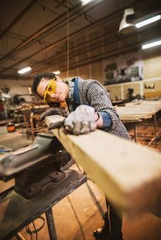Vista del ritratto del lavoratore di carpentiere femminile professionale invecchiato mezzo laborioso attraente felice che guarda e che sceglie legno nell'officina o nel garage.