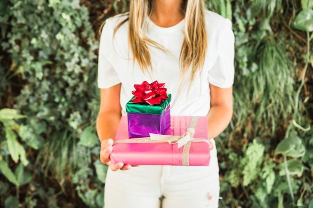Vista del tronco della mano della donna che tiene i contenitori di regalo