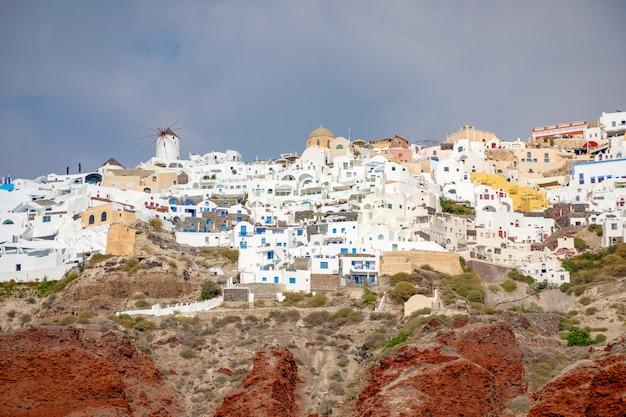 Vista del villaggio di oia con le case bianche sulla caldera rossa delle rocce dell'isola di santorini, grecia