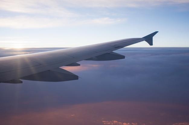 Vista dell'ala dell'aeroplano sopra la bella nuvola al raggio di sole e al tramonto. viaggio e trasporto