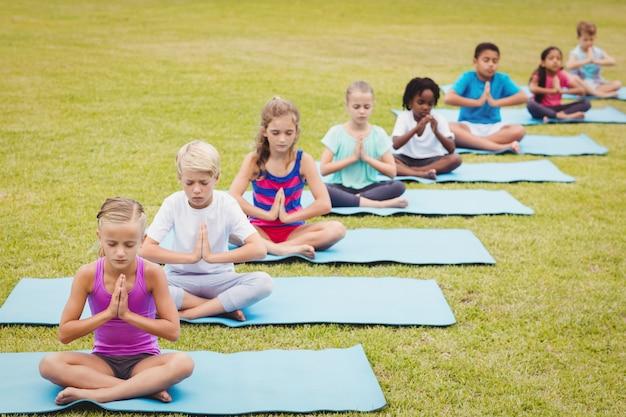 Vista dell'angolo alto dei bambini che fanno yoga