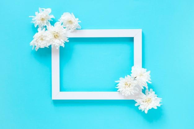 Vista dell'angolo alto dei fiori bianchi e della cornice in bianco su fondo blu