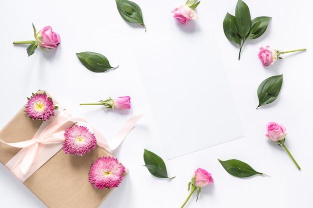 Vista dell'angolo alto dei fiori e delle foglie con il contenitore di regalo sulla superficie di bianco