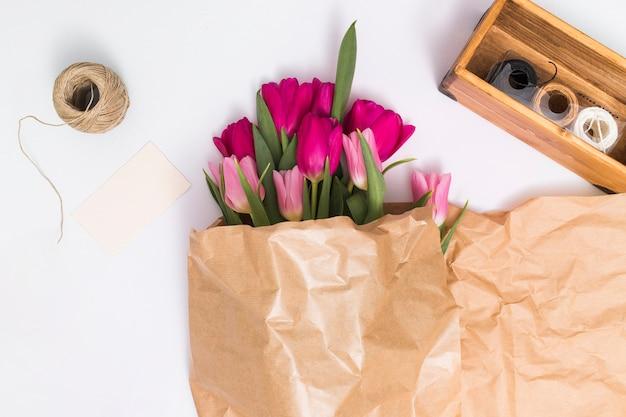 Vista dell'angolo alto dei fiori rosa del tulipano in carta marrone; con varietà di corde su sfondo bianco