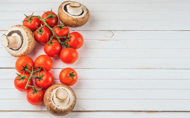 Vista dell'angolo alto dei pomodori e del fungo rossi freschi su fondo di legno