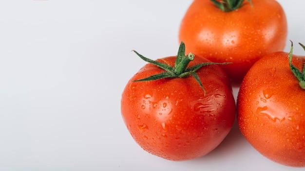 Vista dell'angolo alto dei pomodori rossi freschi su fondo bianco