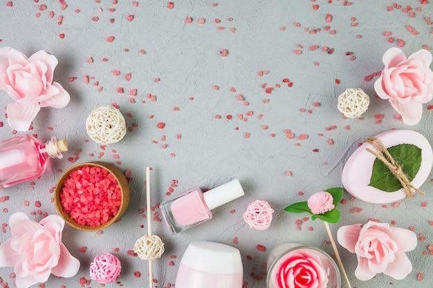 Vista dell'angolo alto dei prodotti di bellezza con i fiori su fondo grigio