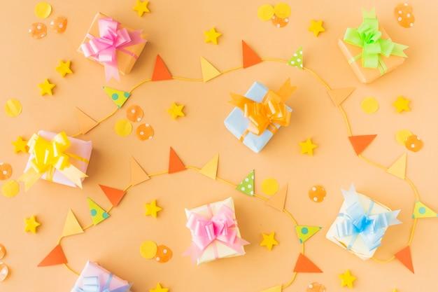 Vista dell'angolo alto dei regali di compleanno e degli accessori del partito su fondo colorato