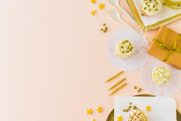 Vista dell'angolo alto dei regali e dei muffin di compleanno su fondo colorato