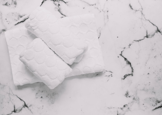 Vista dell'angolo alto dei tovaglioli bianchi su fondo di marmo
