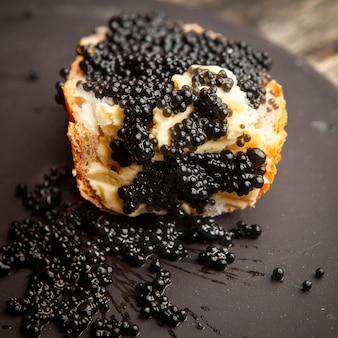 Vista dell'angolo alto del caviale nero su un pane e su un fondo scuro