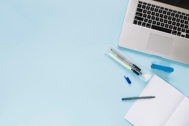 Vista dell'angolo alto del computer portatile e delle cancellerie su fondo blu