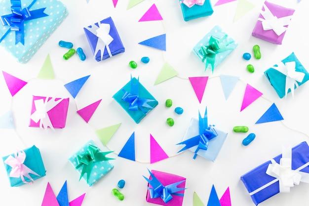 Vista dell'angolo alto del contesto di bianco del figlio dei regali di compleanno e delle caramelle