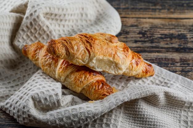 Vista dell'angolo alto del croissant sull'asciugamano di cucina e di legno