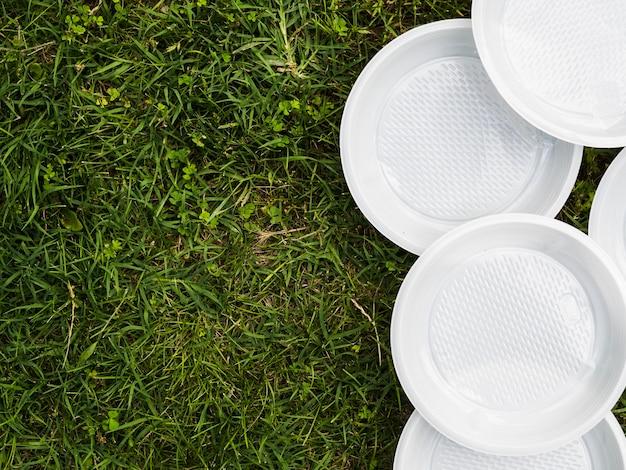 Vista dell'angolo alto del piatto vuoto di plastica bianco su erba