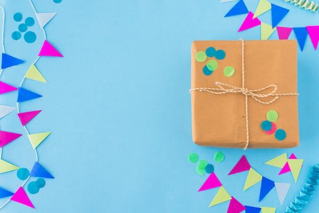 Vista dell'angolo alto del regalo e della stamina di compleanno su fondo blu