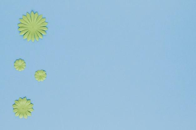 Vista dell'angolo alto del ritaglio verde decorativo del fiore su fondo blu