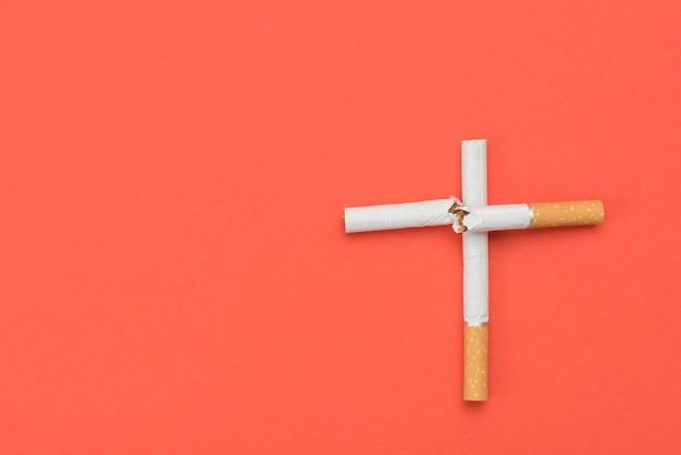 Vista dell'angolo alto del segno trasversale fatto dalla sigaretta su fondo arancio
