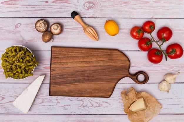 Vista dell'angolo alto del tagliere di legno che circonda dalla pasta cruda e dall'ingrediente sulla tavola