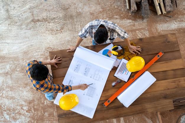 Vista dell'angolo alto dell'ingegnere e dell'architetto che discutono piano di costruzione al cantiere, gruppo di costruttori che hanno conversazione sul piano di costruzione.