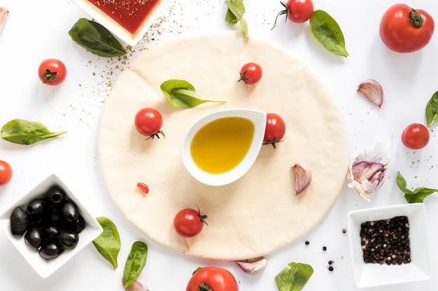 Vista dell'angolo alto dell'ingrediente crudo della pizza sul contesto bianco