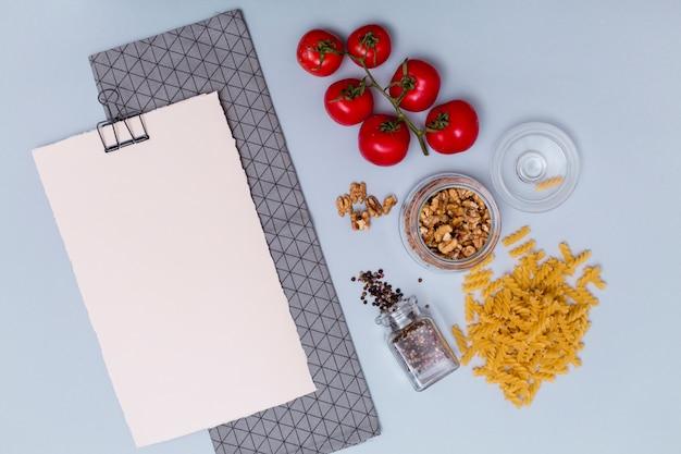 Vista dell'angolo alto dell'ingrediente della pasta con carta in bianco bianca e tovagliolo sopra superficie grigia