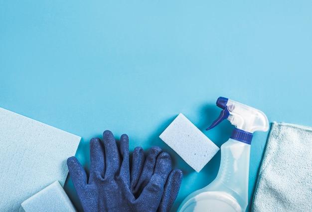 Vista dell'angolo alto della bottiglia dello spruzzo, dei guanti e della spugna su priorità bassa blu