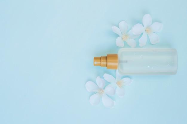 Vista dell'angolo alto della bottiglia di profumo con i fiori bianchi su fondo blu