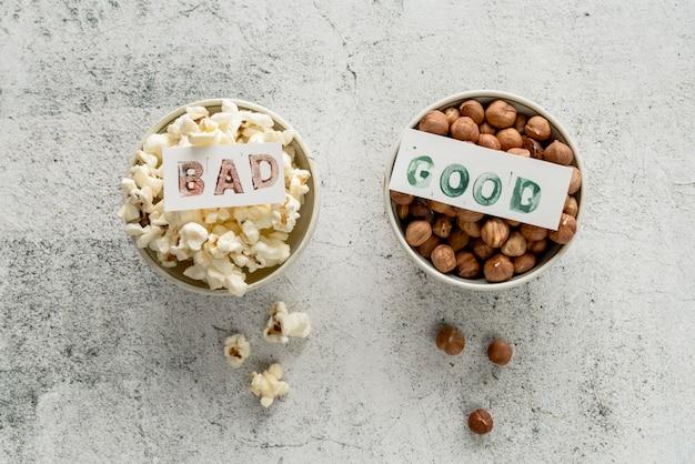 Vista dell'angolo alto della carta di testo difettosa su popcorn e sulla ciotola della nocciola della carta del buon testo