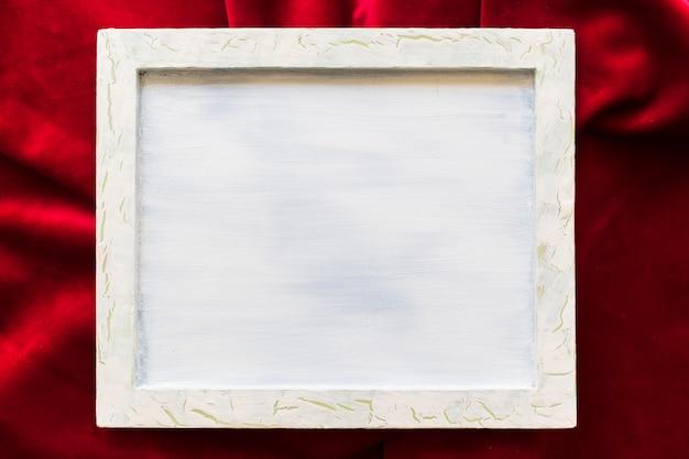 Vista dell'angolo alto della cornice in bianco sul tessuto rosso regolare
