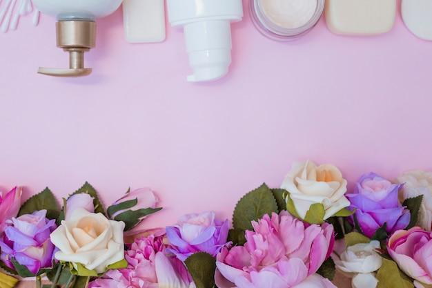 Vista dell'angolo alto della crema idratante e dei fiori falsi su fondo rosa