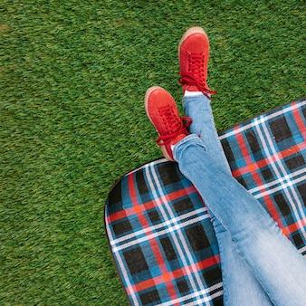 Vista dell'angolo alto della gamba delle donne sulla coperta sopra tappeto erboso