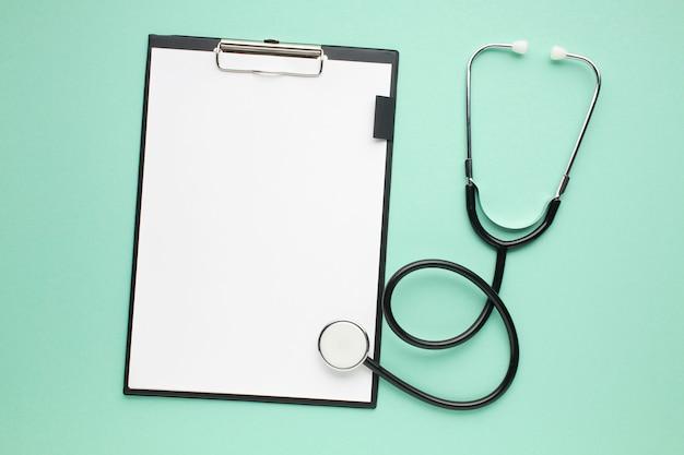 Vista dell'angolo alto della lavagna per appunti con libro bianco e lo stetoscopio su superficie verde