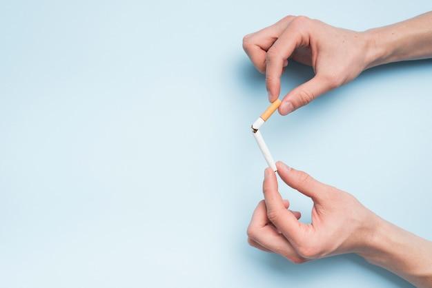 Vista dell'angolo alto della mano della persona che tiene sigaretta rotta contro il contesto blu