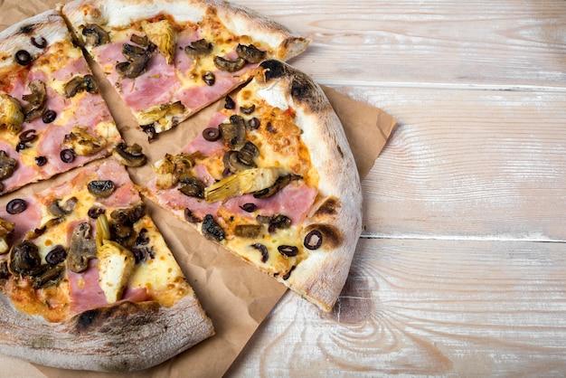 Vista dell'angolo alto della pizza affettata delle merguez dei funghi su carta marrone sopra la tavola di legno