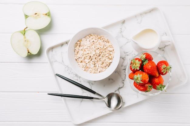 Vista dell'angolo alto della prima colazione sana di mattina sulla tavola di legno bianca