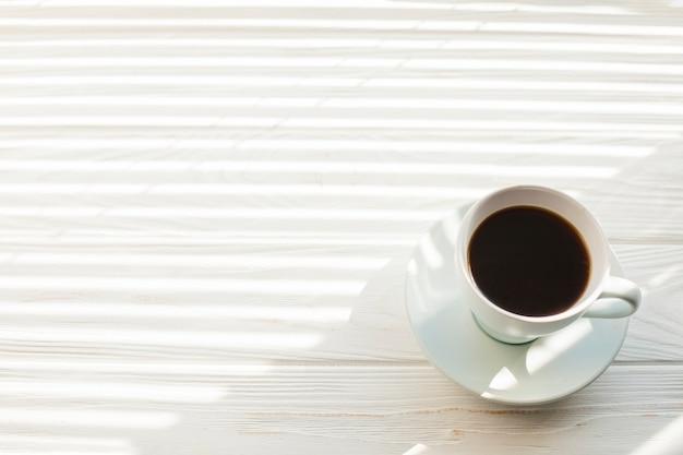 Vista dell'angolo alto della tazza di caffè deliziosa del caffè espresso sopra la tavola di legno bianca