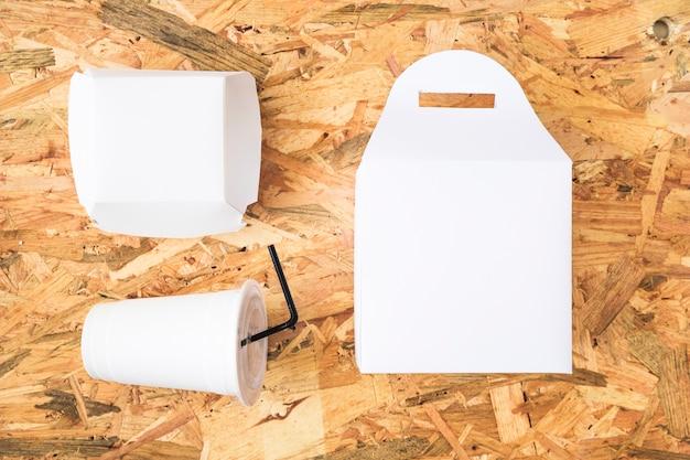 Vista dell'angolo alto della tazza e del pacchetto di disposizione sul piano d'appoggio di legno