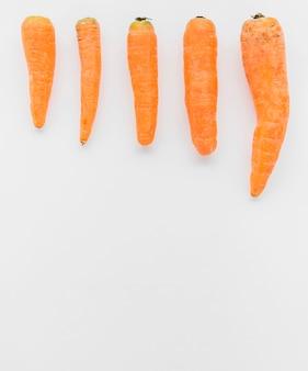 Vista dell'angolo alto delle carote fresche su fondo bianco