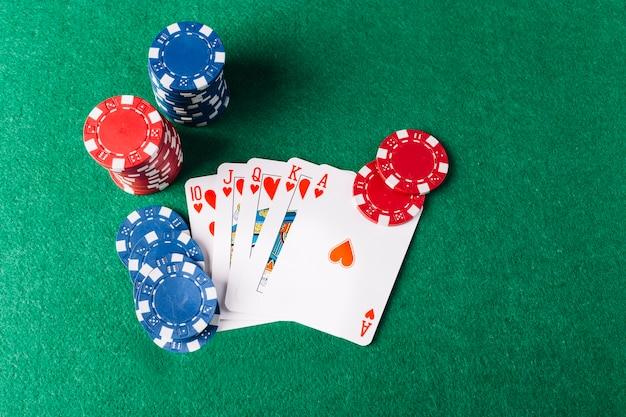 Vista dell'angolo alto delle carte da gioco di scala reale con i chip del casinò sulla tavola della mazza