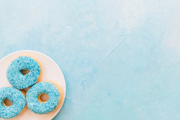 Vista dell'angolo alto delle ciambelle blu sul piatto