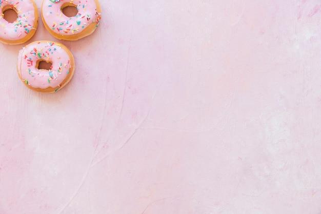 Vista dell'angolo alto delle ciambelle fresche con spruzza su fondo rosa