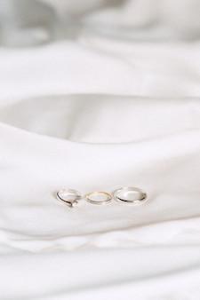 Vista dell'angolo alto delle fedi nuziali su un panno su fondo bianco
