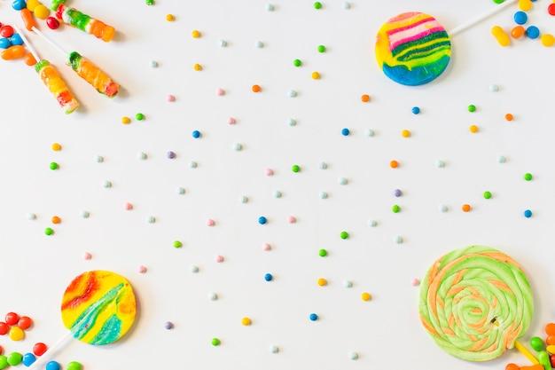 Vista dell'angolo alto delle lecca-lecca e delle caramelle su fondo bianco